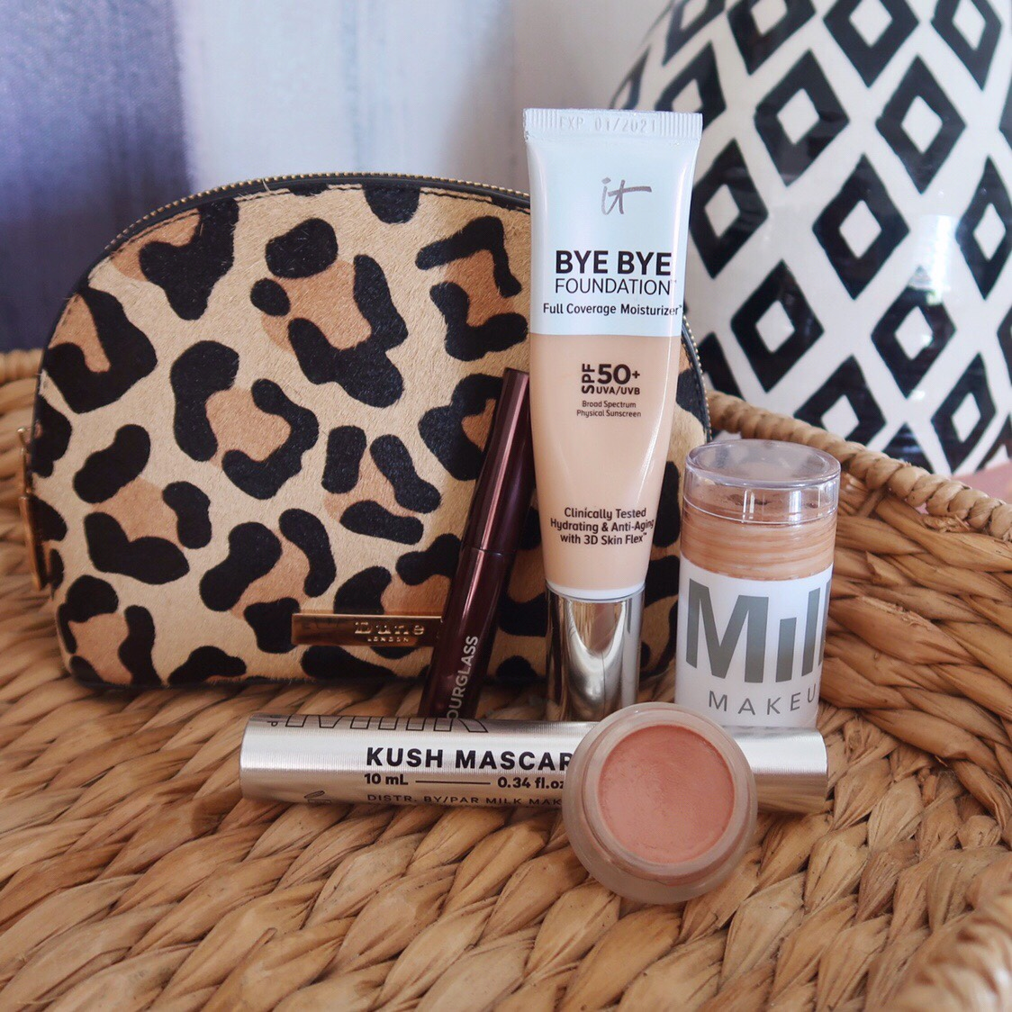 5-product makeup routine displayed in front of a leopard makeup bag, featuring It Cosmetics Bye Bye Foundation, MILK Kush Mascara, MILK Matte Cream Bronzer, rms beauty Lip2Cheek in 'spell' and Hourlgass brow gel.