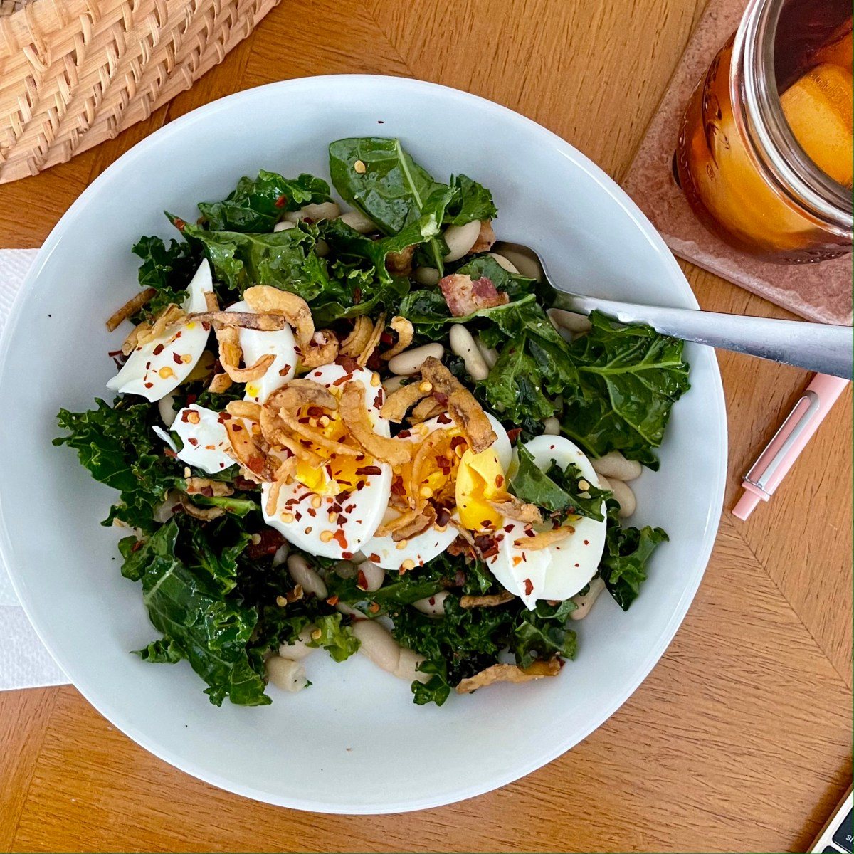 Easy white bean kale salad topped with sliced boiled egg and crispy onion in white ceramic bowl.