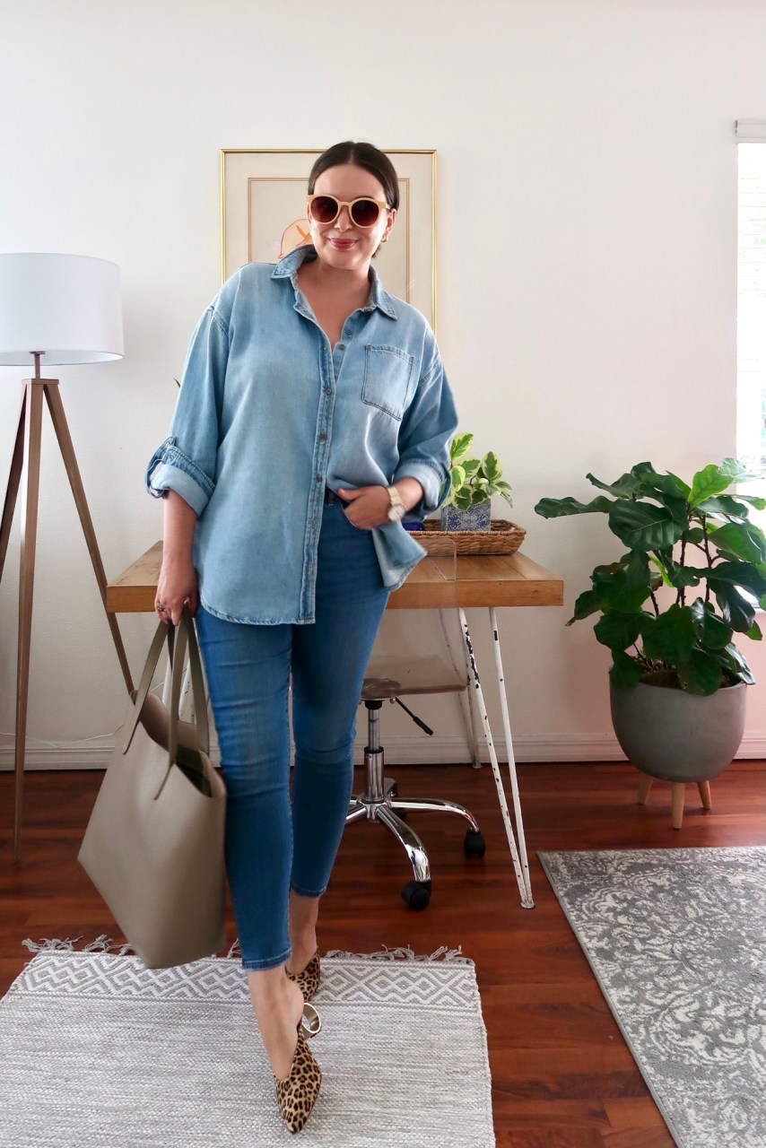 Style blogger wearing oversized denim shirt with skinny jeans and a Cuyana structured leather tote bag