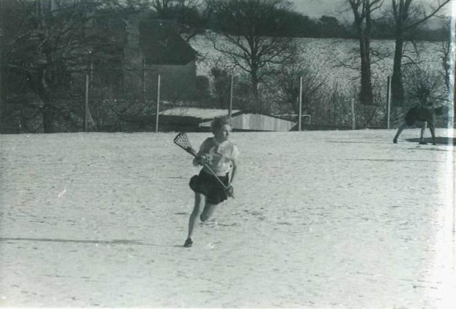 Celia Brackenridge playing lacrosse in the snow