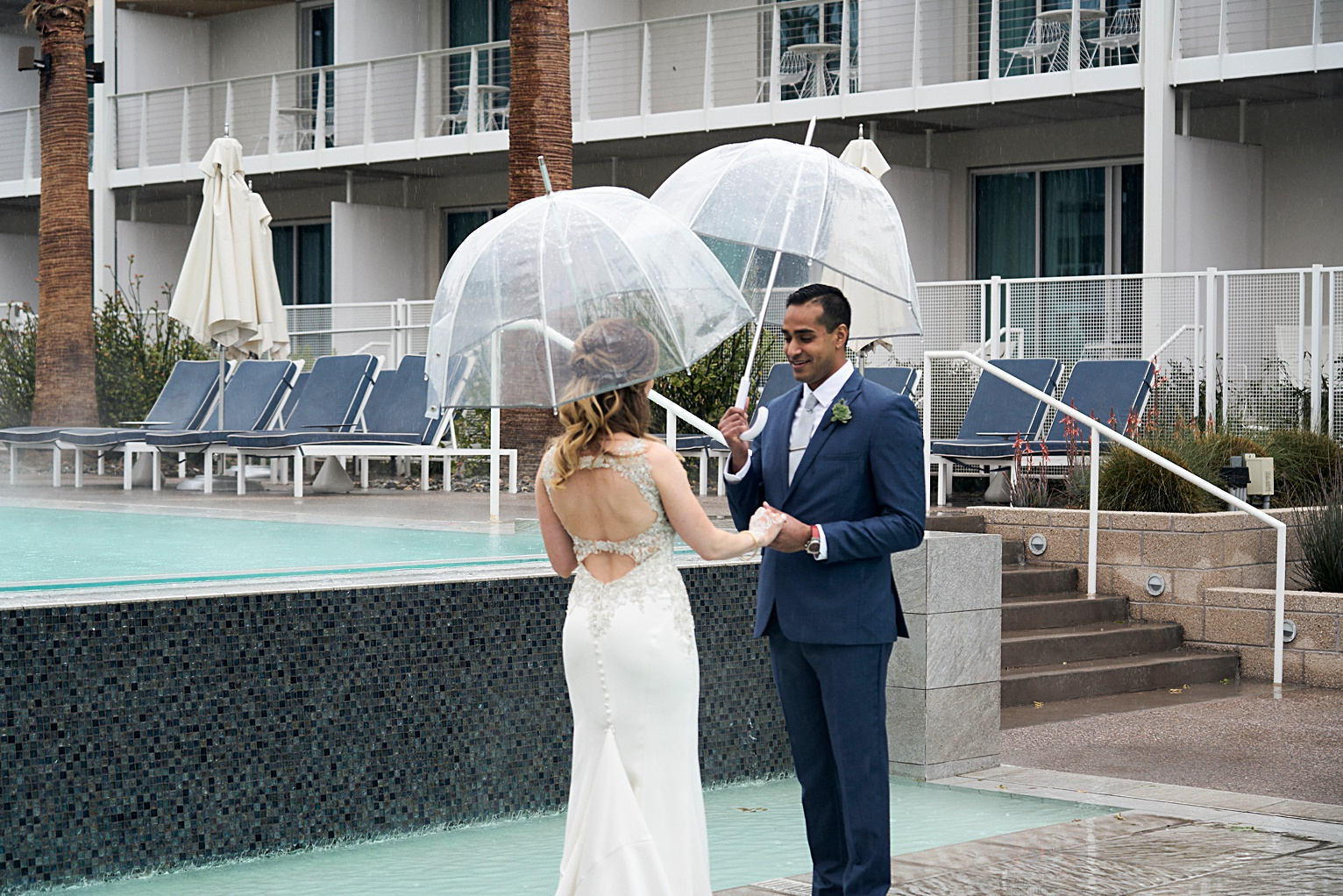 first look on wedding day with umbrella in the rain