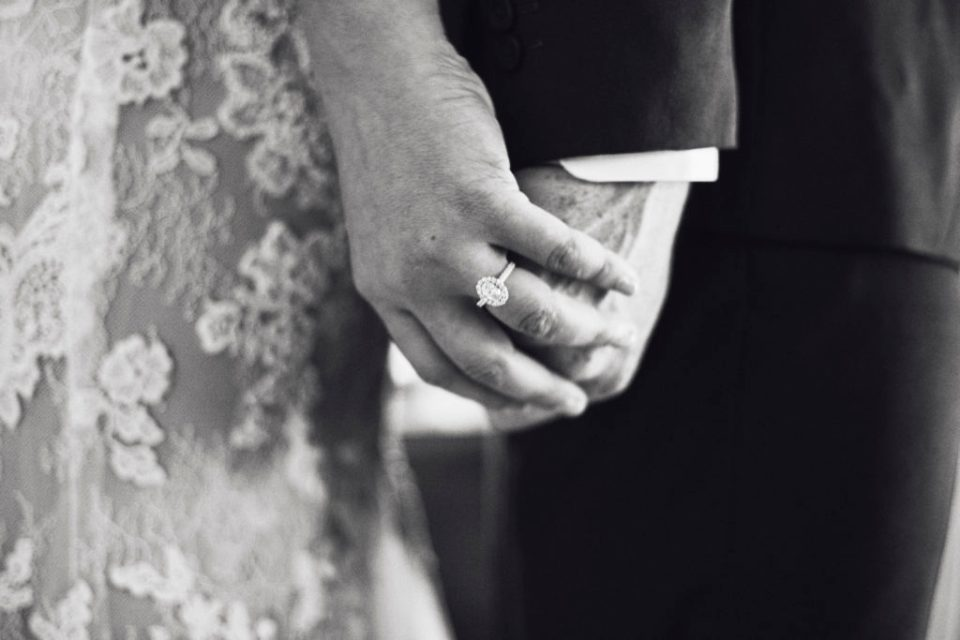 couple holding hands with wedding rings