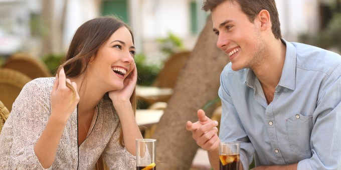 Couple dating and flirting while taking a conversation and looking each other in a restaurant