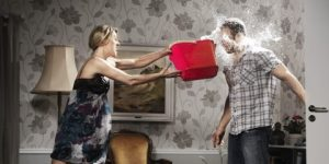 woman thowing a bucket of water at her partner