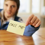 Man holding a note that reads 'call me' --- Image by © Royalty-Free/Corbis