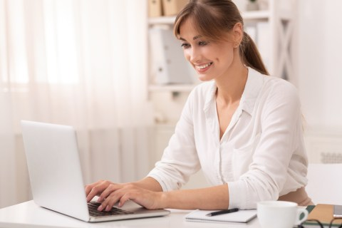 Smiling Businesswoman Using Laptop Working In Office