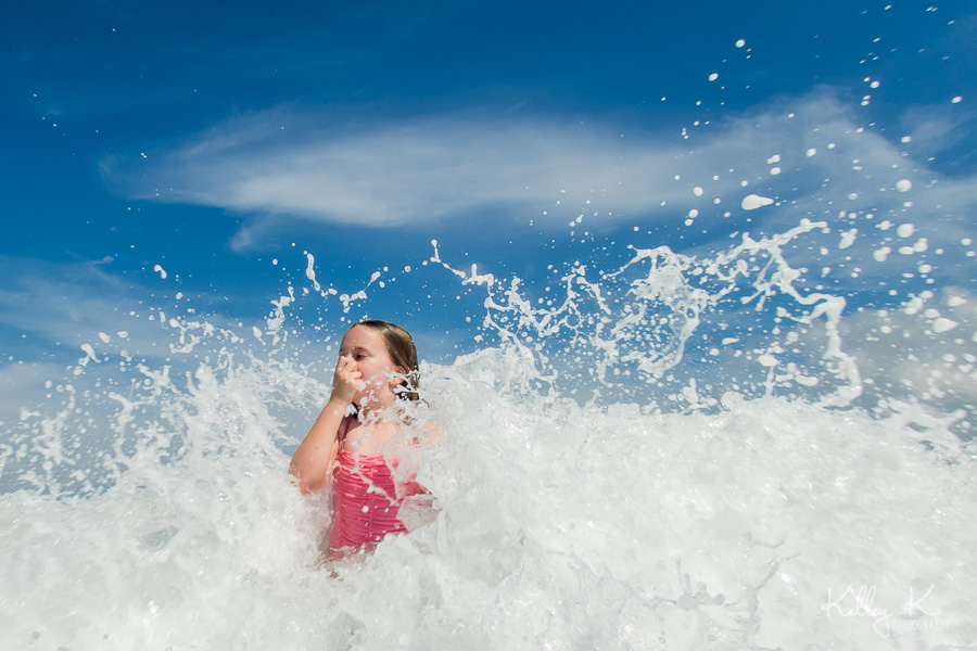 Girl-splashing-ocean-waves-KelleyKPhotography-SmyrnaGA