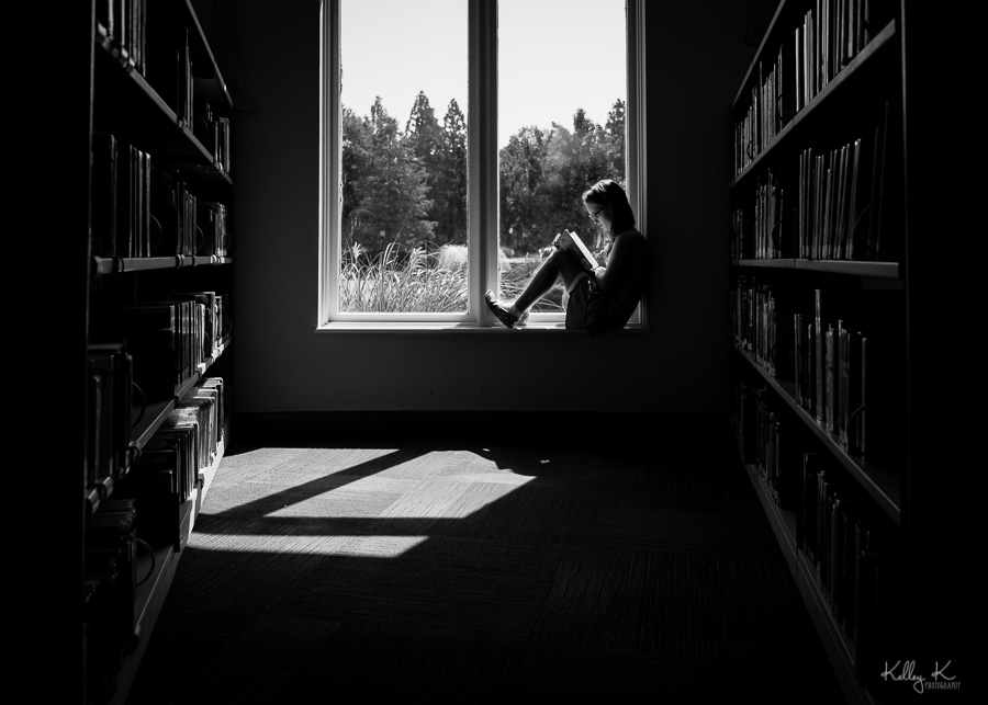 Black and white silhouette of girl reading in a library window