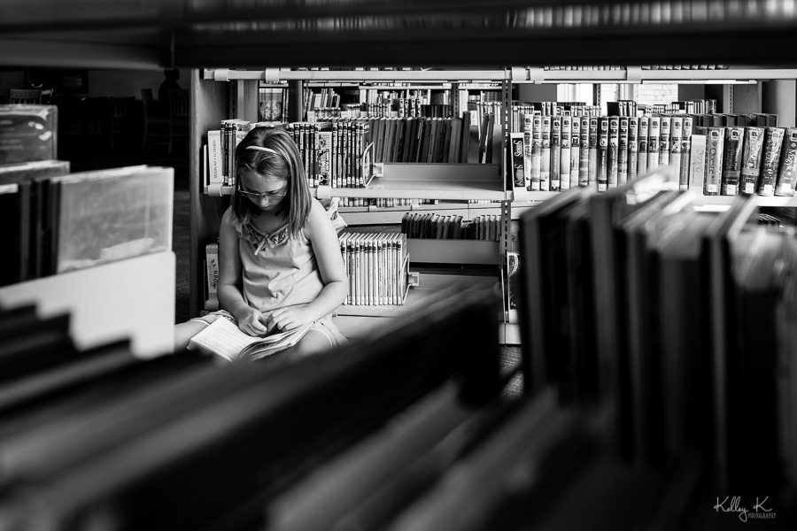 Black and white image of girl reading in a library through the stacks