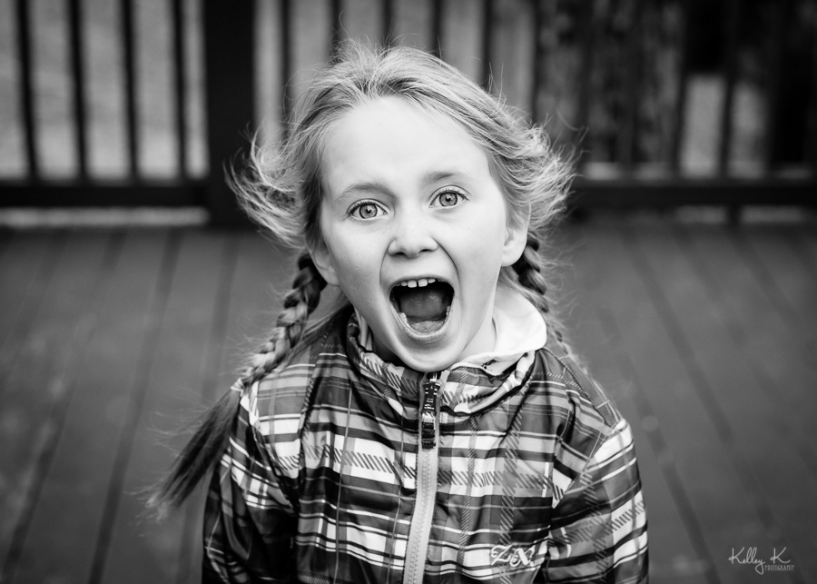 Black and white image of a girl shouting in excitement