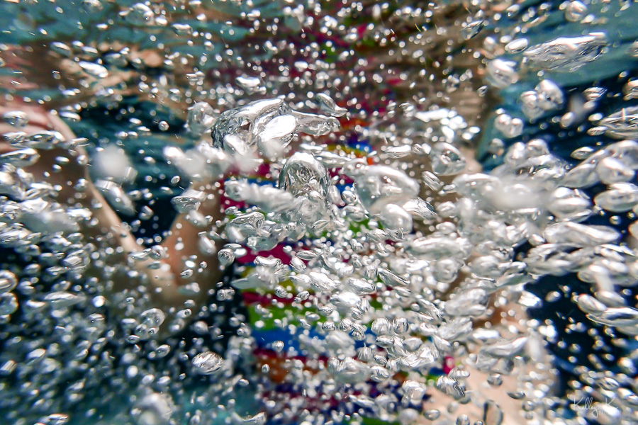 Photograph of tiny underwater bubbles against colorful background