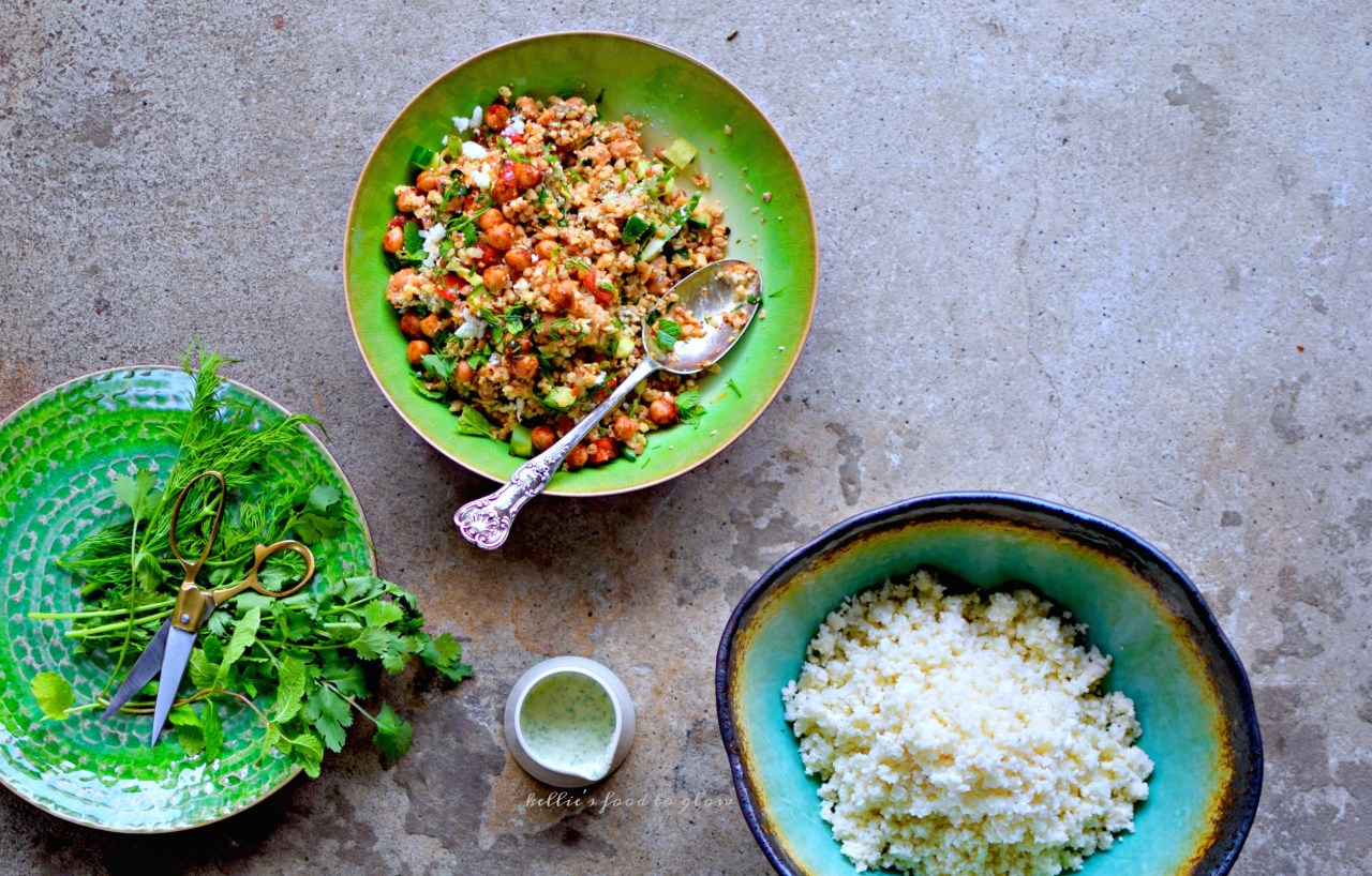 """Use your blender and one simple trick to zap whole cauliflower into perfect """"rice"""" for this throw together summer tabbouleh bowl. Add in harissa chickpeas, pre-cooked quinoa, herbs, veggies and a creamy feta and mint dressing for a cool but slightly spicy lunch or supper. Picnic-perfect and lunchbox-luscious,too."""