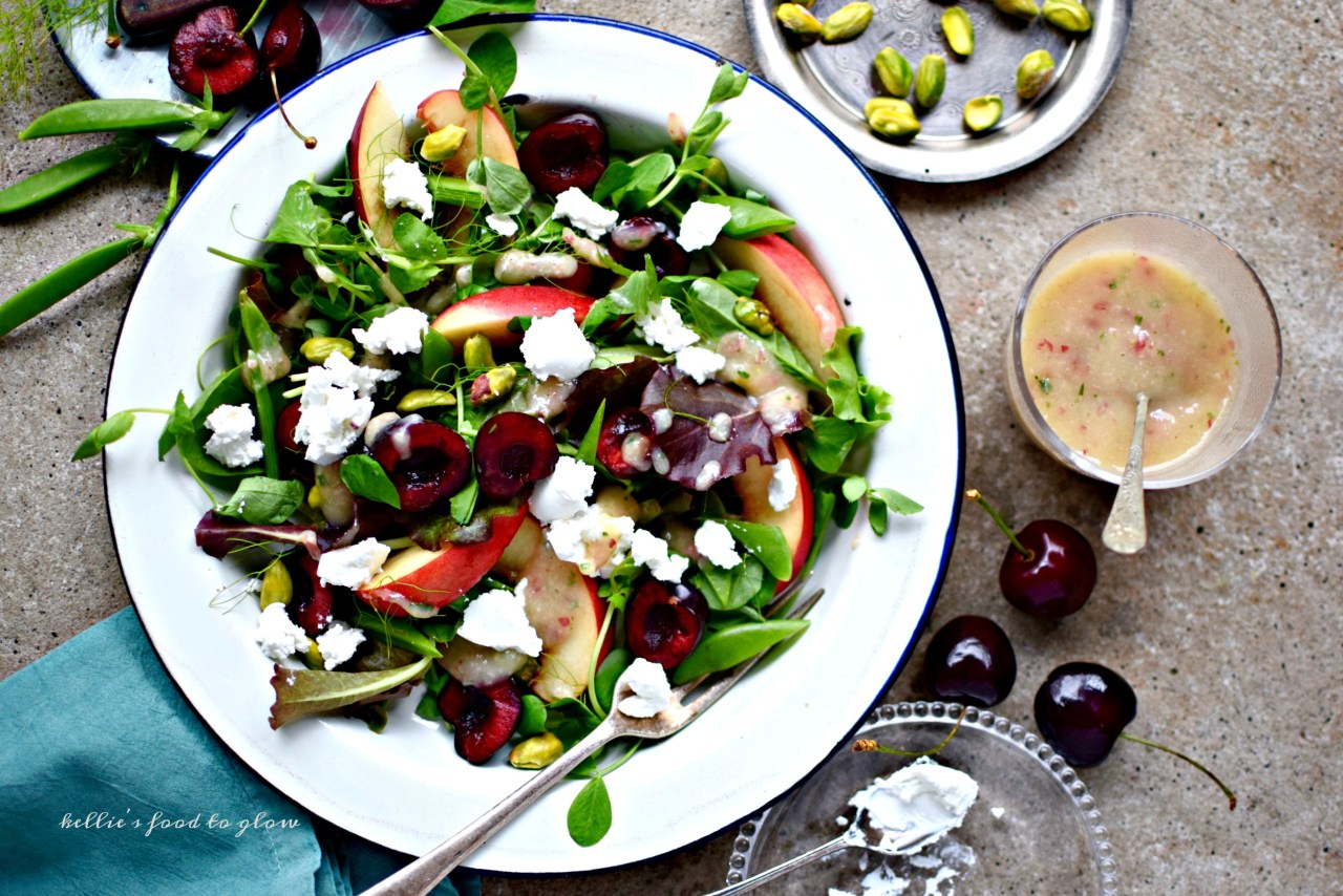 A simple lunch salad recipe highlighting seasonal cherries and peaches along with pistachios,sugar snap peas and a really rather special fat-free and fruity dressing. Add crumbles of goat's cheese or cashew ricotta for a yummy, creamy tang.
