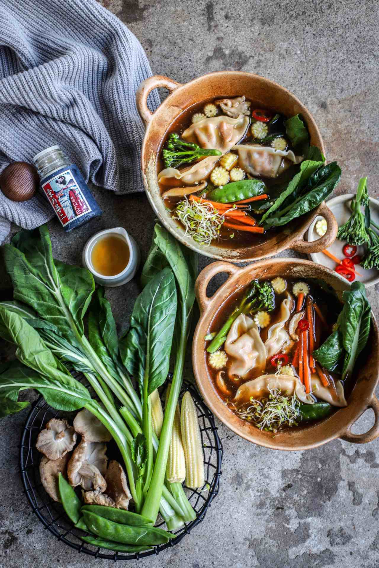 This Shiitake-Ginger Broth is light and deeply-nutritious, floating a whisper of thinly-cut vegetables and a few juicy gyozas. The perfect antidote to heavy winter food. Sip this wholesome, healing Japanese-inspired soup piping hot for best cold-blasting effect. #soup #vegan #shiitake #japanesefood #ginger #broth #healthyrecipe #nutrition