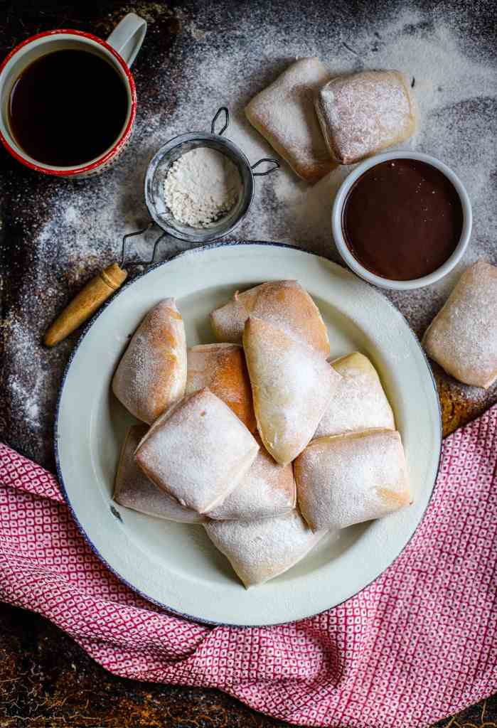 Baked version of New Orleans iconic doughnut, the beignet. Square pillows of soft yeast dough are baked and showered in confectioners' sugar then dipped into a thick, homemade hot chocolate sauce. A traditional Mardi Gras - Fat Tuesday - treat.