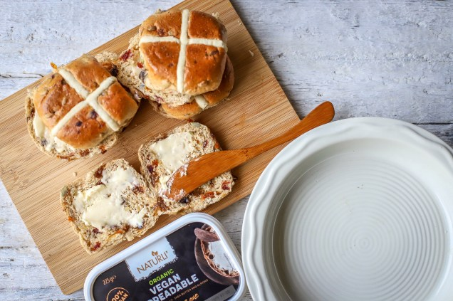 close up of hot cross buns being buttered on wooden board with pie dish to side