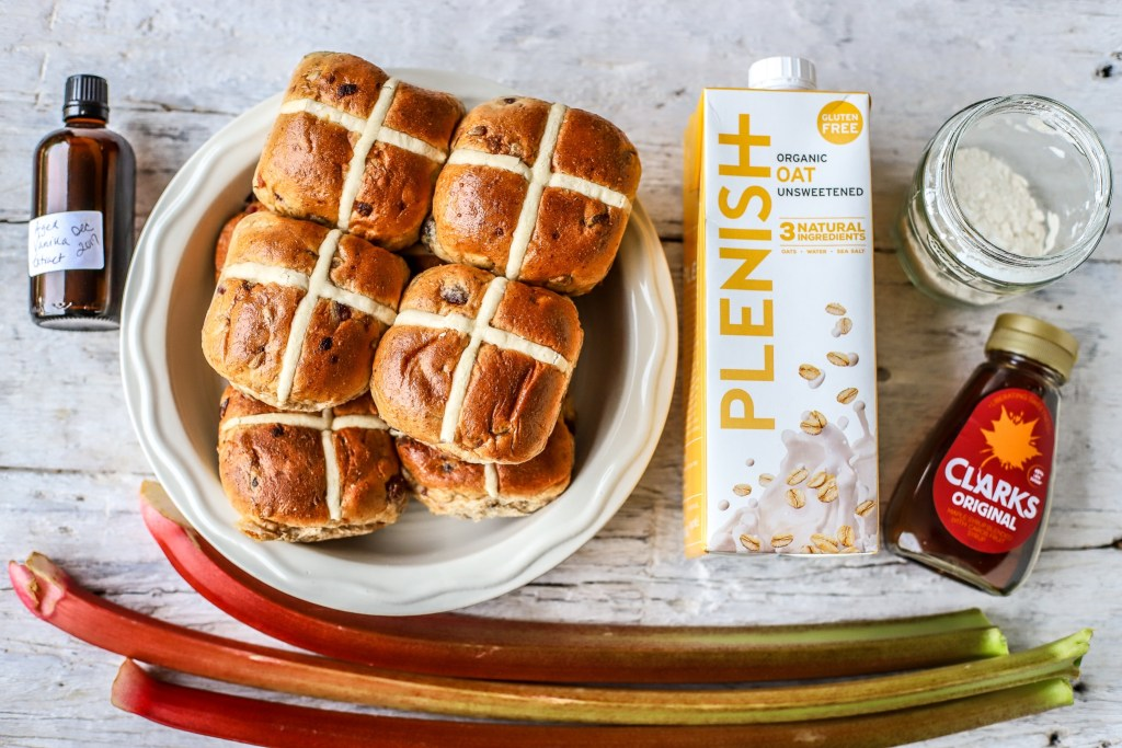 ingredients for hot cross bun and butter pudding on white wooden background, portrait style