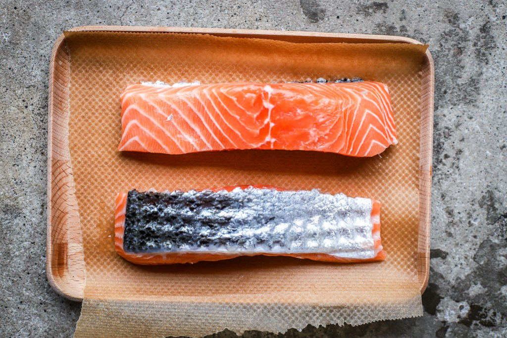 wild Scottish salmon fillets on wooden plate with concrete background