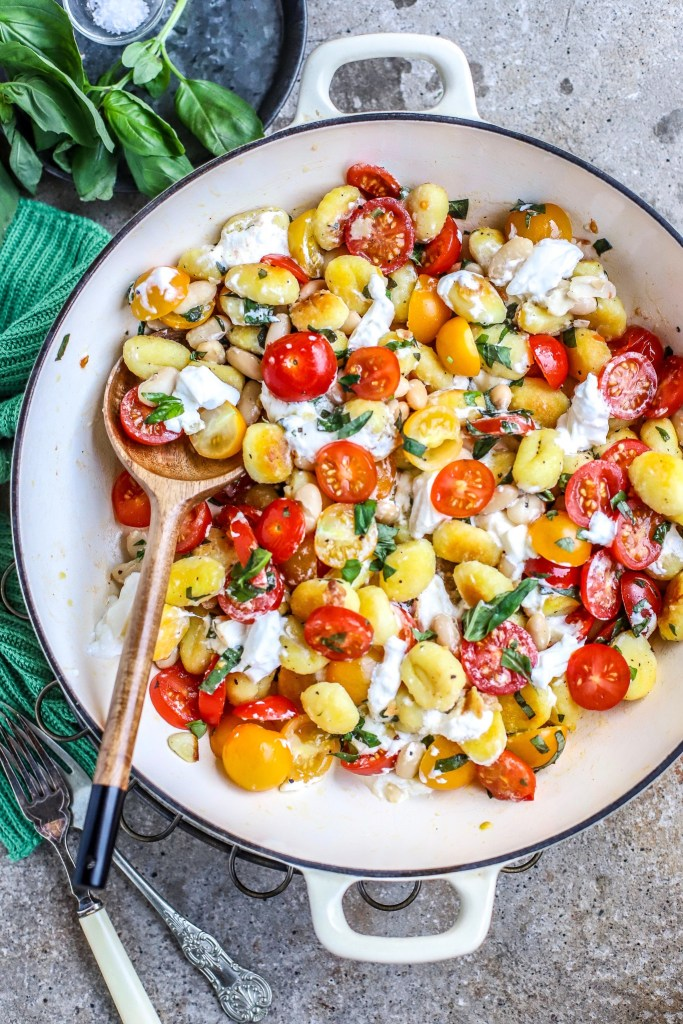 vertical image of gnocchi in skillet with fresh tomatoes, herbs and melting cheese