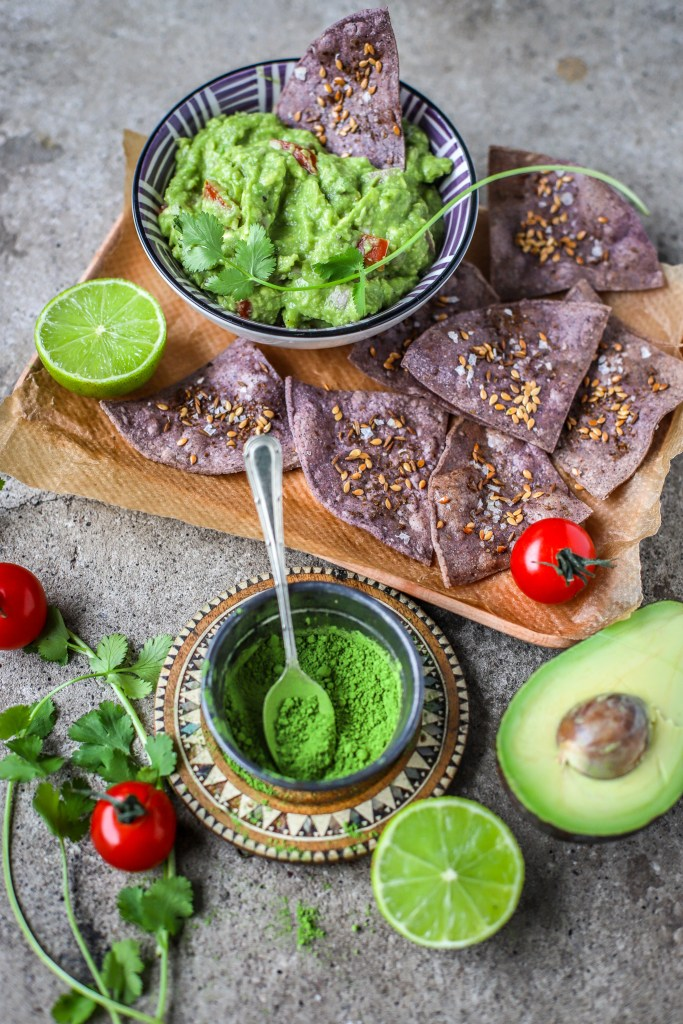 portrait image of green tea enhanced guacamole and fresh accompaniments on concrete backdrop