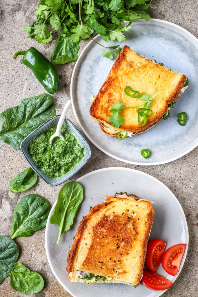 portrait image of spinach and paneer grilled cheese with fresh spinach leaves and mint chutney shown alongside.