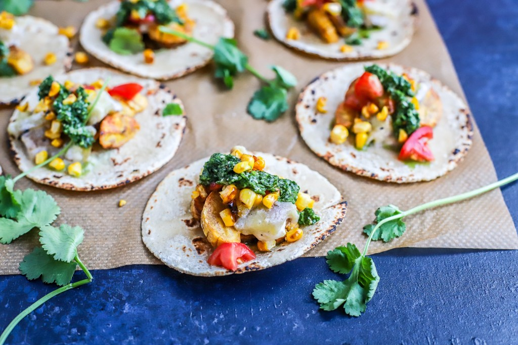 side on view of vegetable soft tacos on baking paper with deep blue background