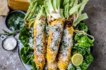 grilled corn with parmesan and dill, on concrete background