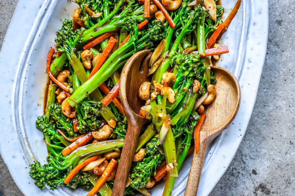 kung pao broccoli and carrots with wooden serving utensils