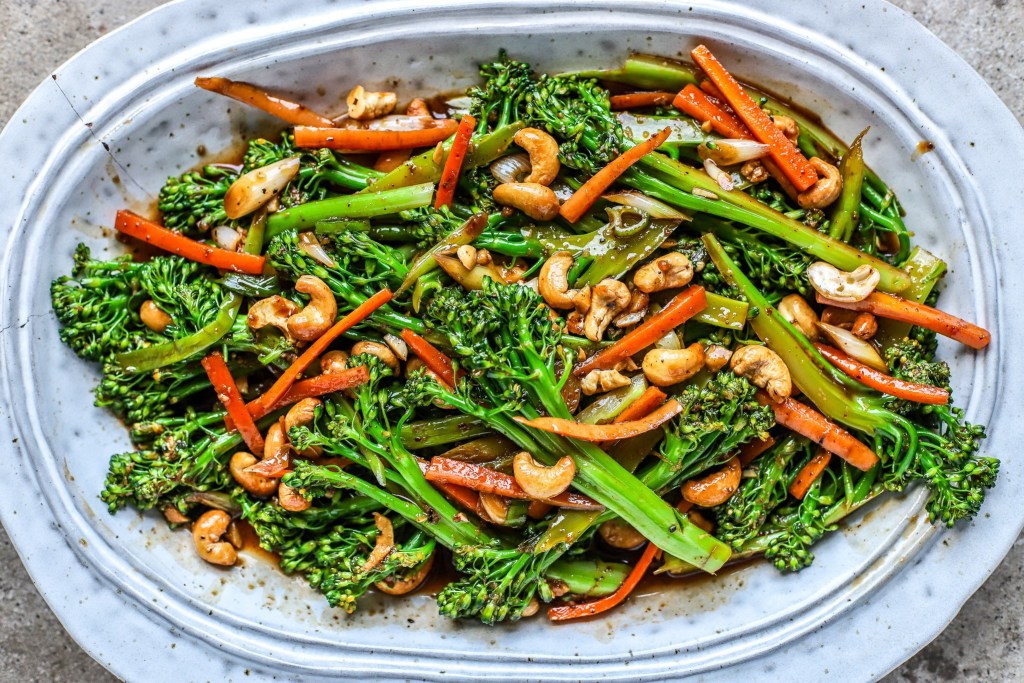 close up of kung pao broccoli with cashews and carrots on grey ceramic platter