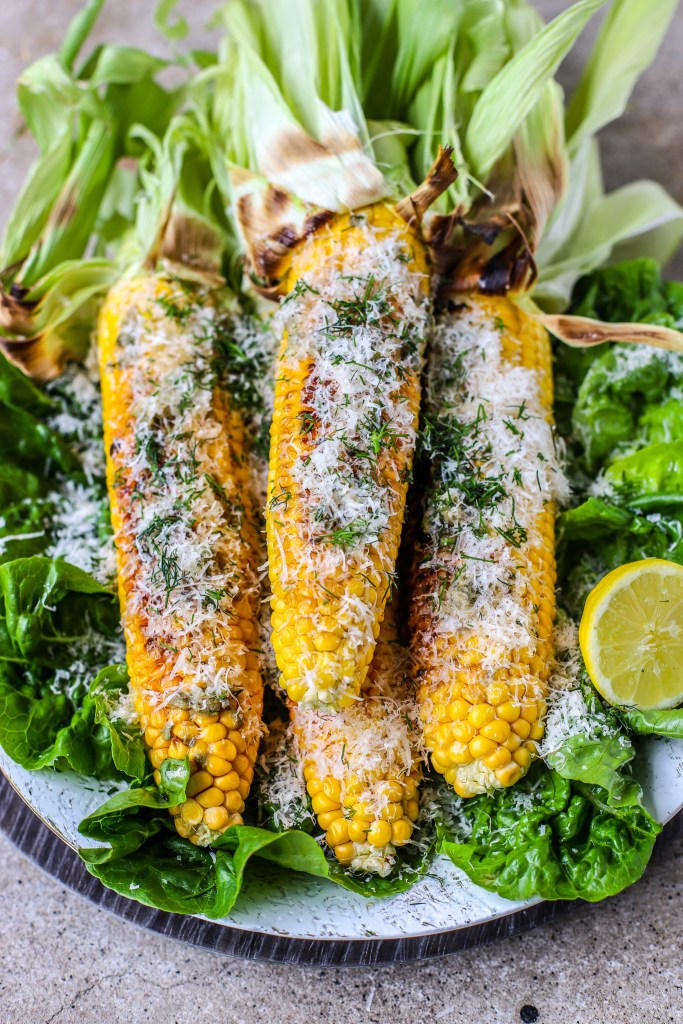 centred grilled corn and 3/4 angle, covered in shredded parmesan and dill