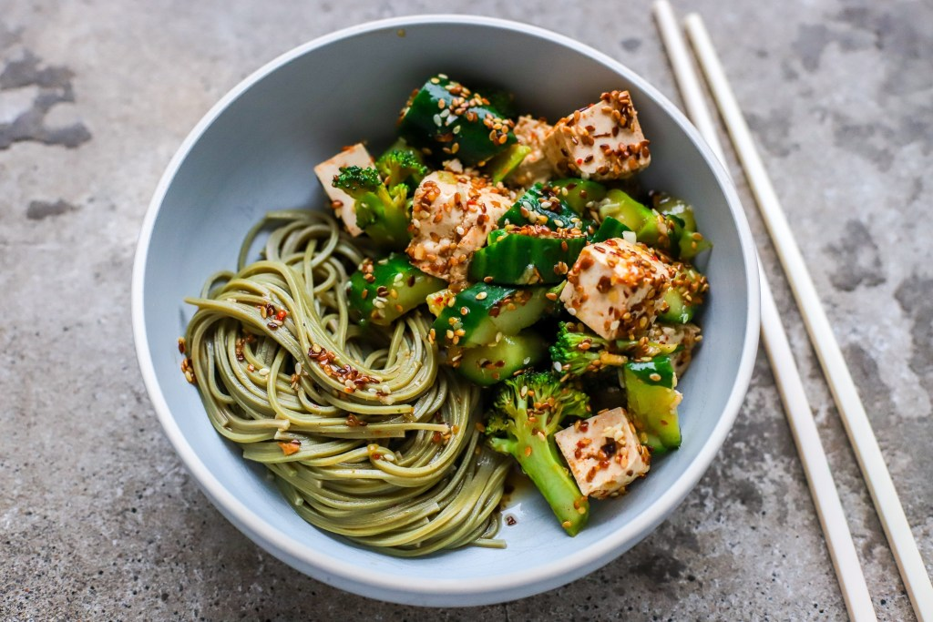 cucumber, broccoli and tofu salad with noodles in grey bowl
