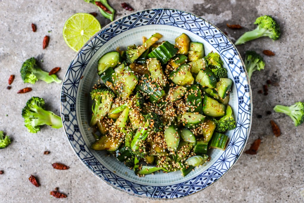 cucumber and broccoli salad in blue and white Chinese bowl surrounded by dreid chillies and broccoli pieces