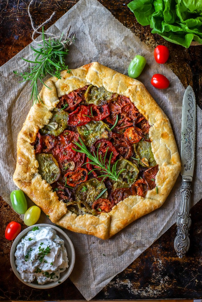 vertical image of tomato tart on baking tray with herbs, fresh tomatoes and ricotta dip
