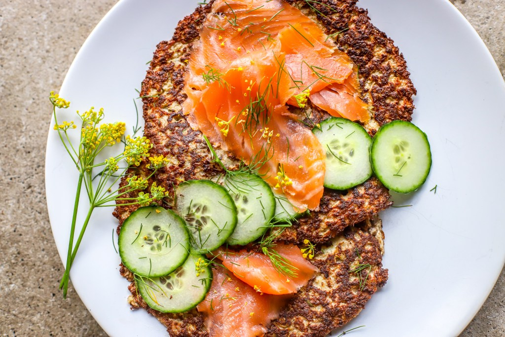 close up of cauliflower rosti with smoked salmon and cucumber slices on white plate