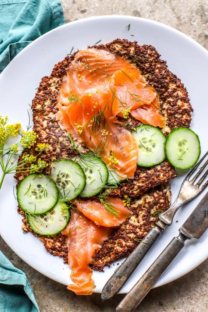 vertical close image of cauliflower rosti, smoked salmon and cucumber on white plate with vintage cutlery and blue napkin