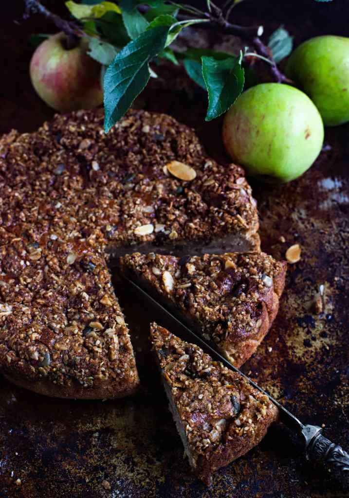 apple cake with slices cut on antique tray with apples - dark mood