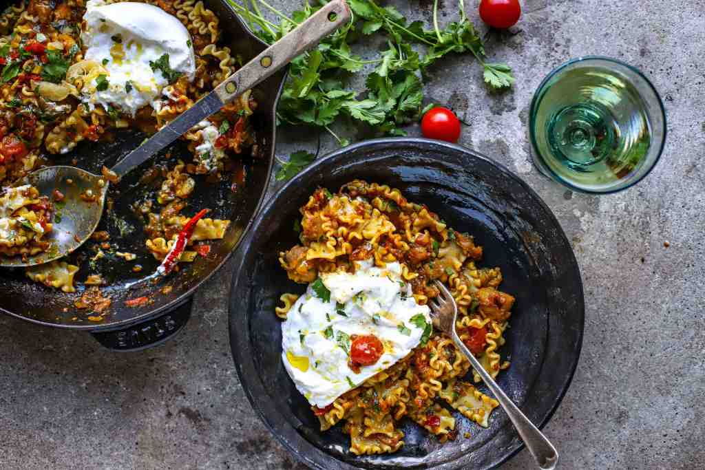baingan bharta with pasta and burrata in skillet and black bowl