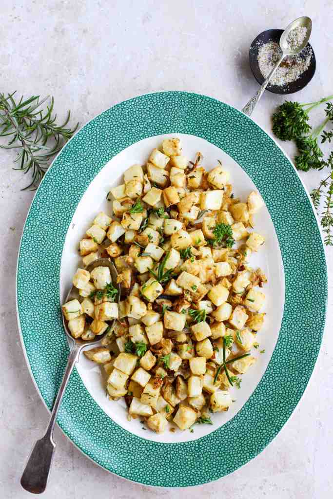 vertical image of celeriac parmentier in white and green dish on pale background