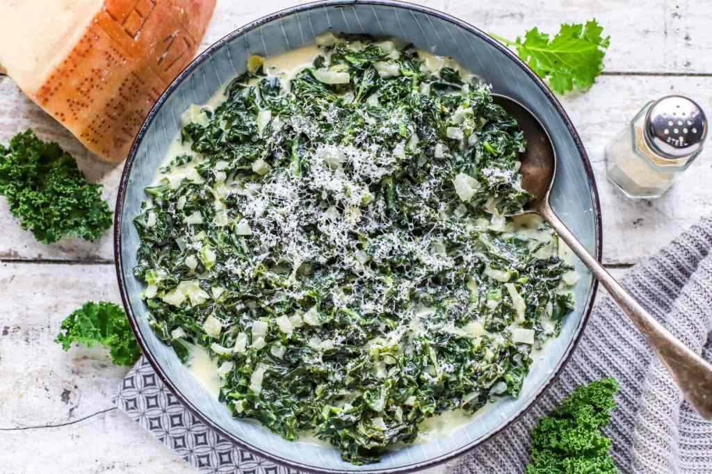 Creamed parmesan kale in grey Scandinavian style bowl with block cheese alongside