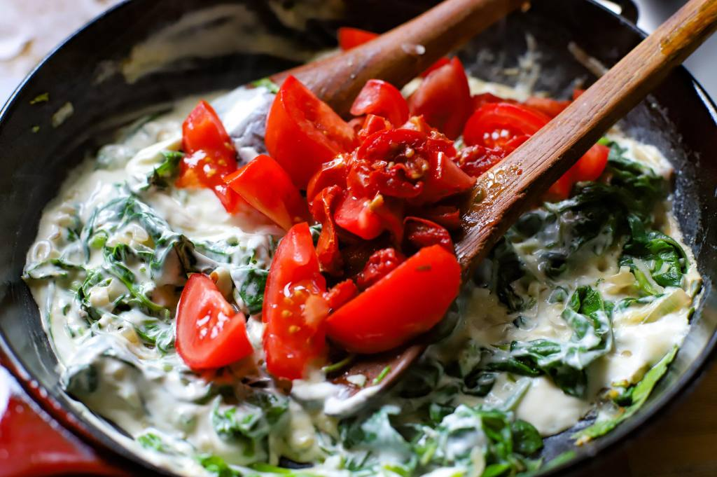 creamy greens with tomatoes in pan