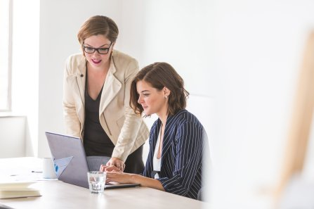 Two women dressed in business clothes, one standing, the other sitting, looking at a computer screen