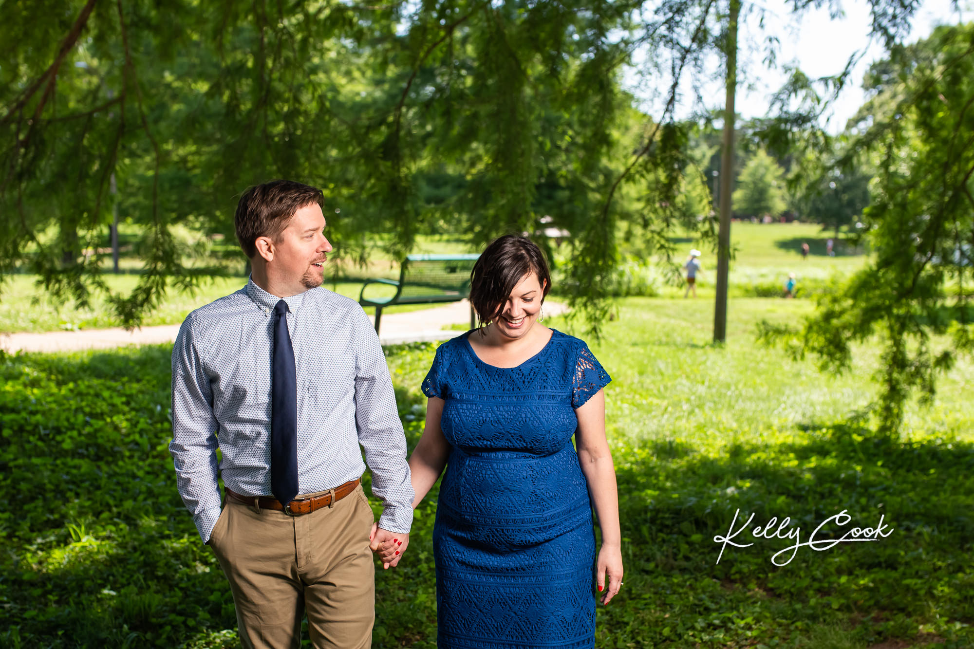 Engaged couple walking together for candid St. Louis engagement photos in Francis Park