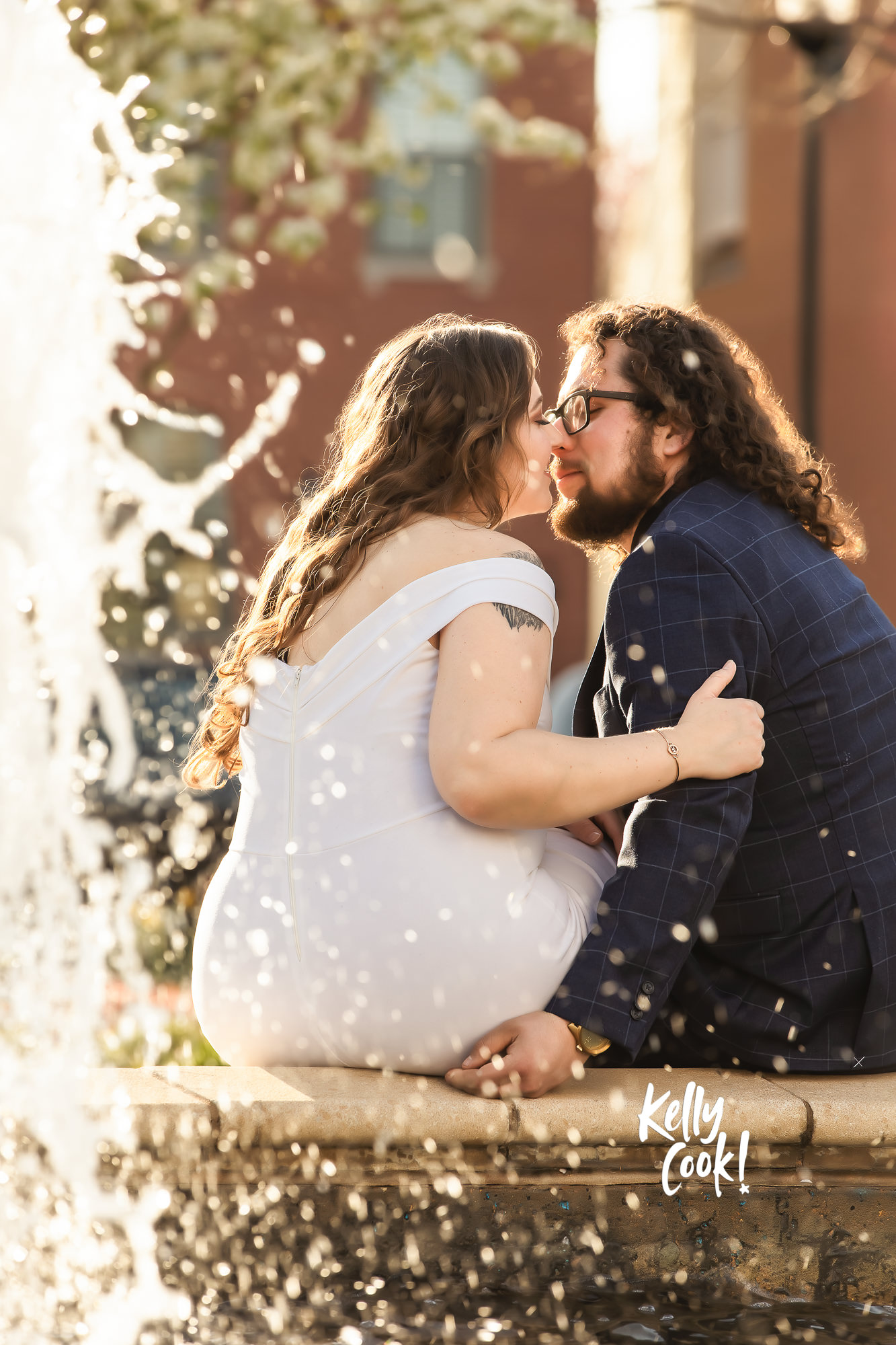 Engaged couple sitting by a fountain kissing in Lafayette Park