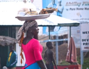 woman carrying a tray on her head