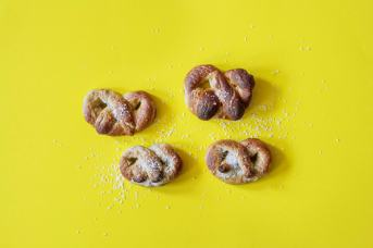 Rustic pretzels on yellow background with scattered coarse sea salt