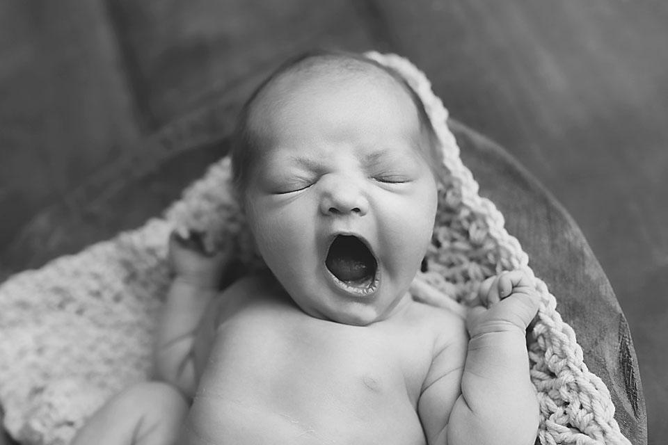 Black and white photo of baby girl yawning
