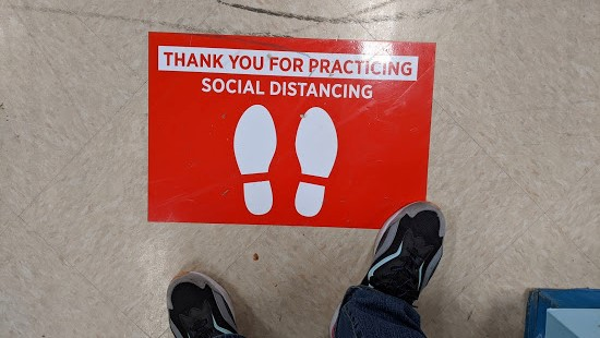 Sign on the floor that says Thank You for Practicing Social Distancing