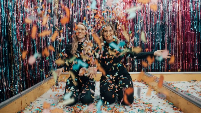 two women throwing confetti