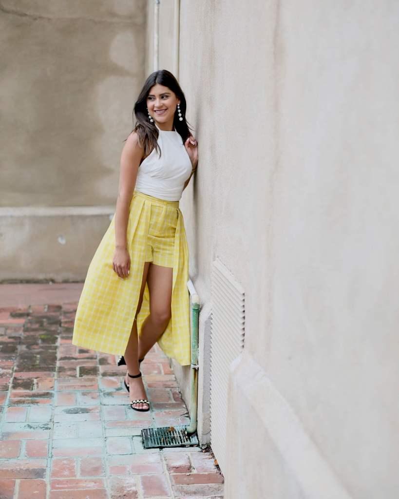 Lifestyle blogger Kelsey Kaplan of Kelsey Kaplan Fashion wearing yellow plaid skort and Stuart Weitzman sandals