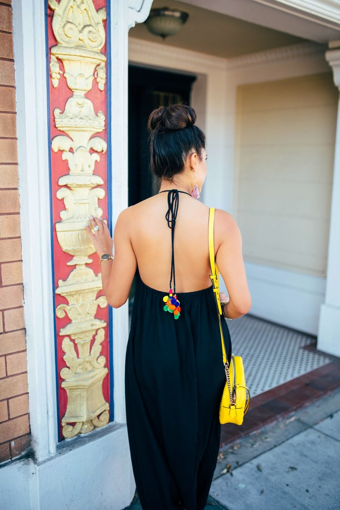 Kelsey Kaplan of Kelsey Kaplan Fashion wearing a black pom pom jumpsuit and yellow gucci purse